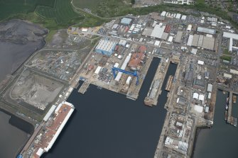 Oblique aerial view of Rosyth Naval Dockyard showing the construction of an aircraft carrier, looking N.