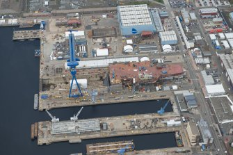 Oblique aerial view of Rosyth Naval Dockyard showing the construction of an aircraft carrier, looking WNW.