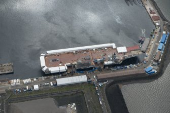 Oblique aerial view of the Main Basin, Rosyth Naval Dockyard showing the construction of an aircraft carrier, looking SSE.