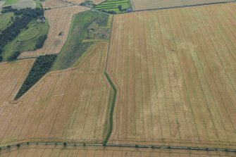 Oblique aerial view of the cropmarks of the pit defined boundaries with The Chesters fort adjacent, looking W.