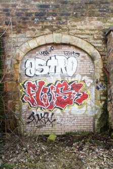 Detail of arched doorway and graffiti tags and throw-ups.