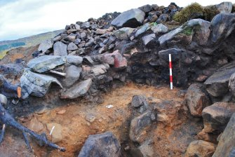 Charcoal-rich and fire-cracked stone layer on west side of rubble wall shown in north facing Trench 1 section; west facing section of material below rubble wall, Comar Wood Dun, Cannich, Strathglass