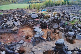 North facing section of Trench 1, south extension; image shows the rubble and soil fill inside the dun walls, with a charcoal-rich layer against the dun inner wall face (centre right, marked by 50cm scale), Comar Wood Dun, Cannich, Strathglass