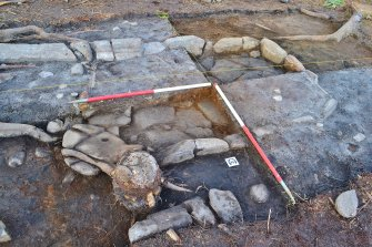 South west corner of hearth section - showing hearth edge and base slabs and rotary quernstone, Comar Wood Dun, Cannich, Strathglass