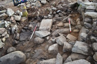 Mid-excavation image after initial clean-back showing possible external wall base (centre) and compact rubble and mid brown soil forming rubble fill between it and the dun outer wall, Comar Wood Dun, Cannich, Strathglass