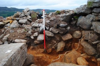 North facing section in Trench 5, showing the rubble spread overlying a compact rubble layer in a slight ditch to the outside of the dun, Comar Wood Dun, Cannich, Strathglass