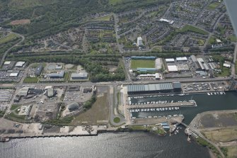 Oblique aerial view of Cappielow Park, Cappielow Jetty, James Watt Dock and Sugar Warehouse, looking SW.