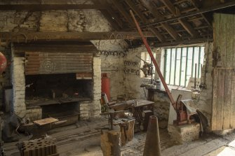 Interior.  Blacksmith's workshop from north west showing (left to right), swage block, anvil, hearth, second anvil and iron beam bending machine.