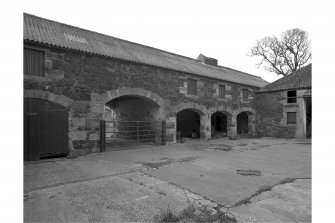 View of cart sheds and pend (arched roof of masonry), in courtyard from NE