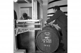 Lagavulin Distillery, Filling Store. View of filling cask with spirit.