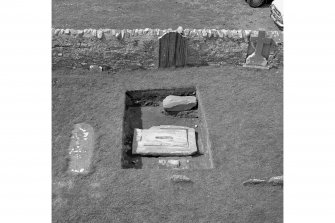 Excavation of cross-base, Kilnave Church, Kilnave. View from East of the basal slab of the cross-slab, showing the centre slot and surrounding structural groove.