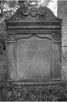 Glencorse old parish church East face, gravestone of Patrick Proudfoot and Janet Hunter d.1742; winged cherub in pediment, corinthian pillasters flanking inscription panel.