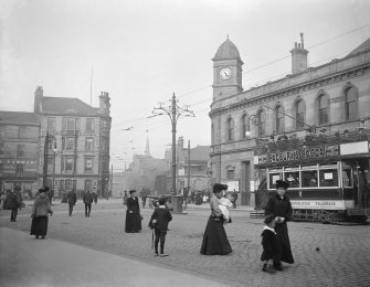 View of Leith Central Station, Edinburgh, from Leith Walk, with street scene and tram advertising Cadbury's Cocoa. The station opened in 1903 and closed for regular passenger traffic in 1952. Visible is also the Queen's Hotel