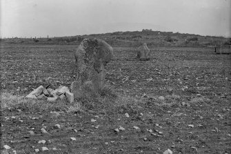 View of standing stone and Pictish symbol stone. Ardlair Recumbent Stone Circle is visible on the hilltop in the distance. Original negative captioned: 'Ardlair Standing Stones Kennethmont view from East. Stone at middle distance is sculptured. May 1906'.