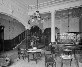 Interior View Of Reception Area With Tables And Chairs Staircase On Left