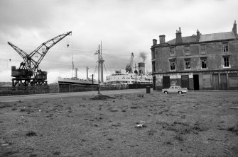View from W showing WNW front of tenement with boat in drydocks on left