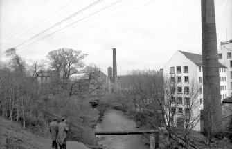 View from W showing part of chimney and NW front of 'Old End' with linen-thread mill in background