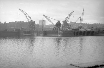 General view from ENE showing part of ESE front and part of NE front of docks with cranes in background