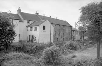 View from N showing part of NW front of altered woollen mill with house on left and brick extension on right