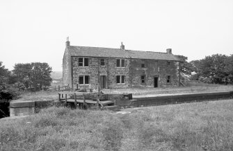 General view from S showing WSW and SSE fronts of lockeeper's house and stables with part of lock in foreground