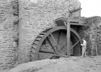 View of waterwheel with figure. Digital image of AG 291.
