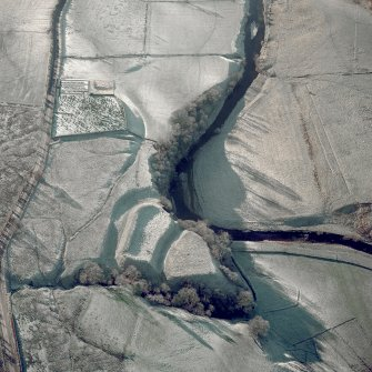Oblique aerial view of Liddel Castle centred on the remains of an earthwork fortification and burial-ground, taken from the NE.