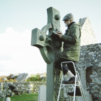 View of Ian G Scott, on ladder, making corrections to his drawing of the Kildalton Cross.