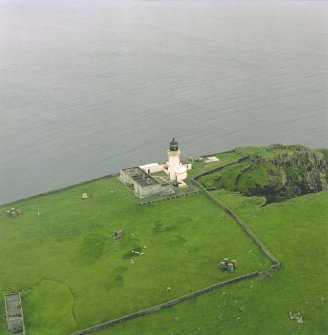 Oblique aerial view centred on the lighthouse with the remains of the dun adjacent, taken from the NNE .