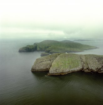 General oblique aerial view of the lighthouse with the island of Mingulay and those to the N in the background, taken from theS .
