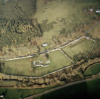 Oblique aerial view centred on the remains of the abbey with the walled garden and house adjacent, taken from the SSW.