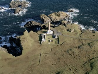 Oblique aerial view centred on the lighthouse with the enclosure adjacent, taken from the SW.