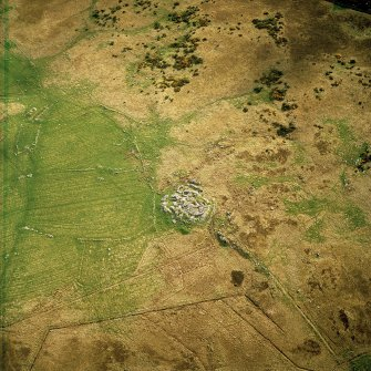 Oblique aerial view centred on the remains of the dun, settlement and field system with hut-circle and farmstead adjacent, taken from the NE.