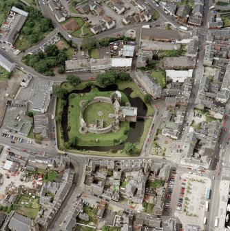 Oblique aerial view of Rothesay centred on the remains of the castle and chapel, taken from the E.