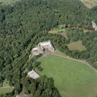 Oblique aerial view centred on the country house and garden with bridge adjacent, taken from the SE.