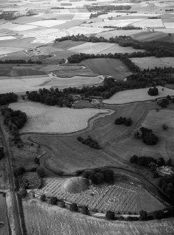 Oblique aerial view centred on the remains of the motte and bailey castle and the cemetery, looking to the NNW.
