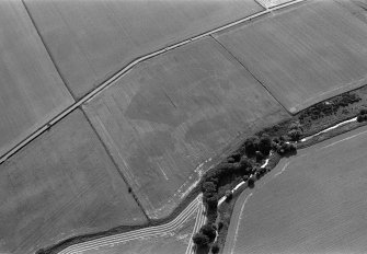 Oblique aerial view centred on the cropmarks of the enclosures, ring ditches and pits at Kirkton and Balmullie Mill, looking to the SSW.