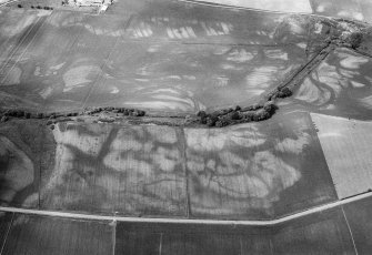 Oblique aerial view centred on the cropmarks of the enclosures, ring ditches, pits and rig at Kirkton and Balmullie Mill, looking to the NW.