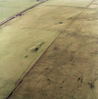 Oblique aerial view centred on the remains of the cairns, taken from the SE. Digital copy of photograph.