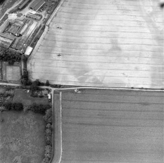 Phantassie, oblique aerial view, taken from the NE, centred on the cropmarks of an enclosure and a possible building. A dovecot is visible in the centre of the photograph and Phantassie farmsteading is shown in the top left-hand corner.