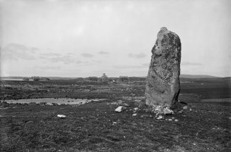 North Uist, Westford. General View of standing stone with blackhouses in the distance