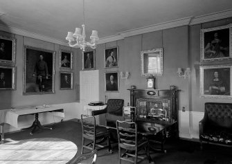 Interior. View of a room with portraits on wall.