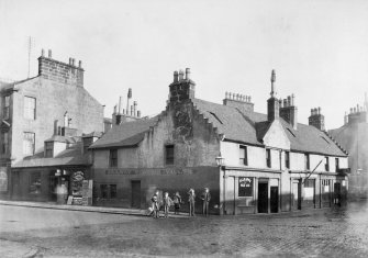General view of children standing on street corner in Paisley.  The Railway Station Vaults is visible on the corner. Titled: 'Corner of St James Place and Old Sneddon St.' Inscribed on verso; 'Valuable... This site is now occupied by the present building where the war-time corner canteen was.'