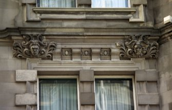 View of carved heads above first floor windows beside main entrance, E side of building (North Bridge).