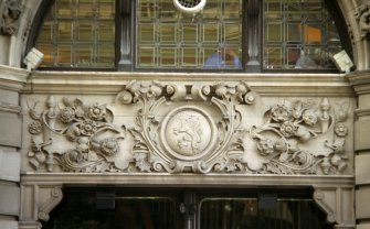View of carved panel to left of entrance to The Scotsman Hotel, E side of building (North Bridge).