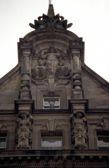 View of upper part of N facade, showing three sculpted female figures representing Peace, with Mercury figures above and caryatids below.