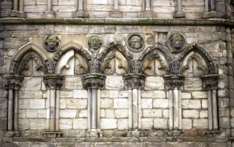 View of four carved heads in roundels, between ground floor arches on W tower of Holyrood Abbey.