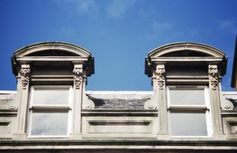 View of top of 72 Princes Street, showing grotesque masks either side of attic windows.