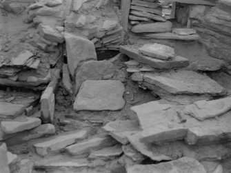 Excavation photograph: House 2, Tumbled stones in S. W. corner; Deliberate blocking of passage adjoining house 1 visible top.