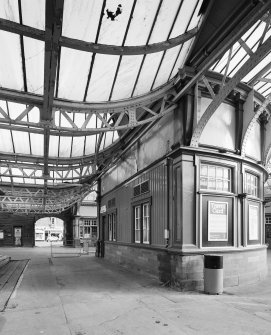 Interior. View from West of raised portions of platform canopies where they meet the central concourse, and the rear of the semi-circular booking office.