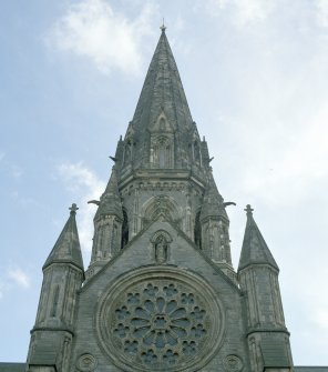 Detail of NW transept's end elevation showing gable with wheel window, niche, roundels and pinnacles, with main tower rising behind.
